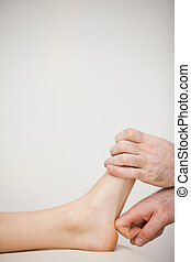 Chiropodist using his index finger to massage a foot in a...