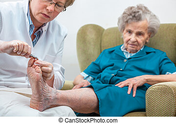 Chiropody - Nurse assists an elderly woman with chiropody ...