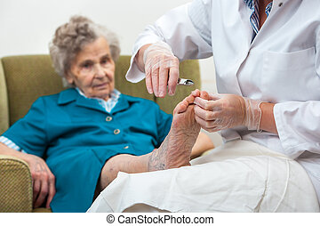 Chiropody - Nurse assists an elderly woman with chiropody...