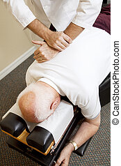 Closeup of chiropractors hands adjusting a senior man's spine.