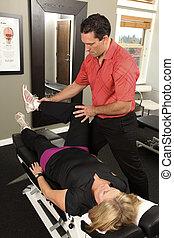 Chiropractor adjusting a female patient
