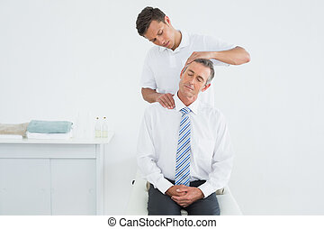 Chiropractor doing neck adjustment - Male chiropractor doing...