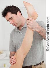 Chiropractor extending the leg of a patient