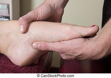 Chiropractor massage the patient bridge of foot