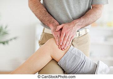 Chiropractor massaging a charming woman's knee