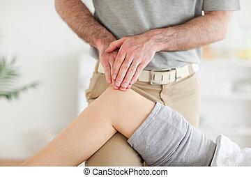 Chiropractor massaging a cute woman's knee