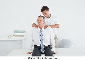 Chiropractor massaging a mature patients shoulder