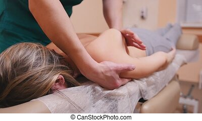 Chiropractor massaging a woman lying on a massage table, flexing the shoulder