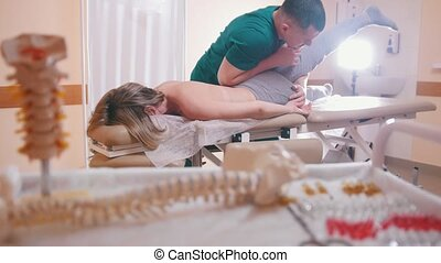 Chiropractor massaging a young woman lying on a massage...