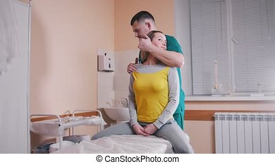Chiropractor massaging a young woman twisting and turning her neck in the medical office