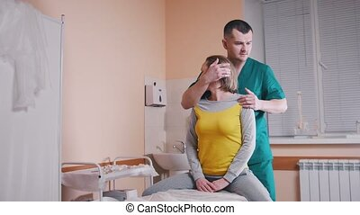 Chiropractor massaging a young woman twisting her neck,...