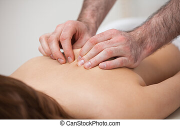 Chiropractor massaging his patient while using his fingertips