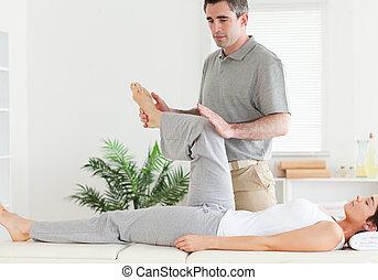 Chiropractor stretching a customer's leg