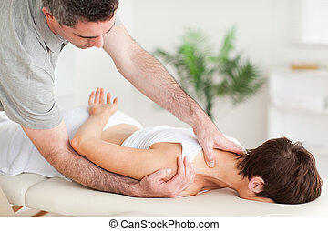 Chiropractor stretching a woman's shoulder