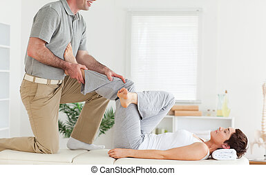 Chiropractor stretching woman's leg