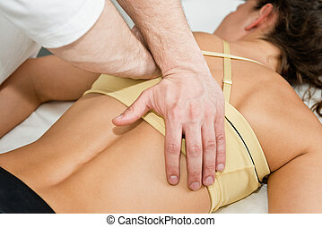 Chiropractor treating patient's back, etiopathy