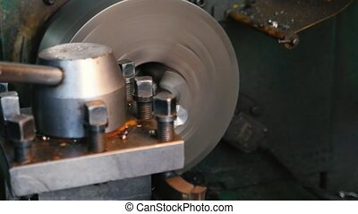 Chisel cutting chips from a metallic rod fixed to a lathe...