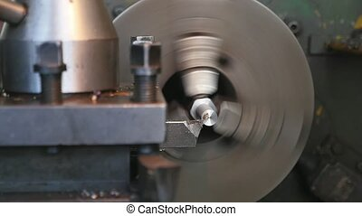 Chisel cutting flakes from a metallic rod fixed to a lathe machine on big plant