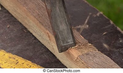 Chisel on wooden plank close up