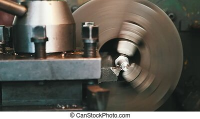 Chisel taking flakes from a metallic rod fixed to a lathe machine on big plant