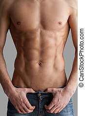 Chiseled chest and abs. Cropped image of muscular man standing isolated on grey background