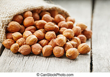 Chiselled hazelnuts in a bag of burlap on a gray wooden table. Organic Fresh Harvested