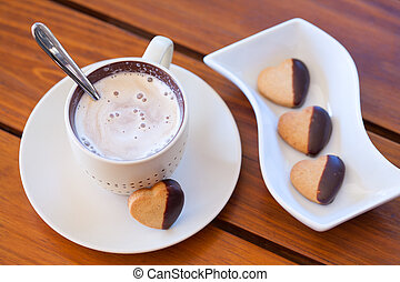 Chocholate dipped heart shaped shortbread cookies and a cup of cappuccino on a wooden table