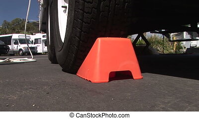 Chock Block - Orange chock wedge placed under tire to stop...