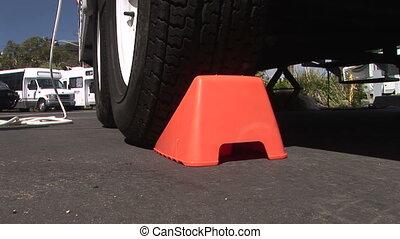 Chock Block - Orange chock wedge placed under tire to stop...