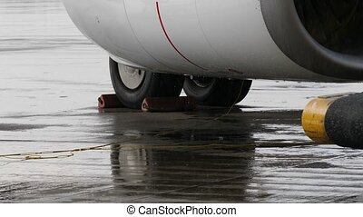 Chocked wheels of airplane undercarriage and part of jet engine under heavy rain