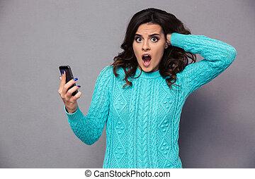 chockerat, kvinna räcka, smartphone