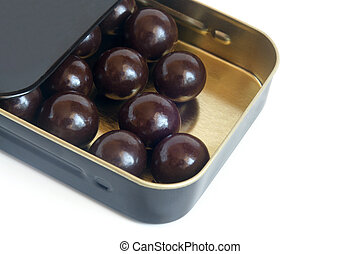 Chocolate balls in box on a white background