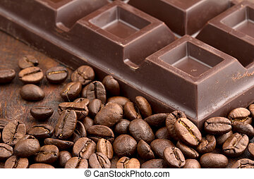chocolate bar and coffee beans on wooden table