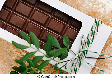 Chocolate bar in a white windowed box, tied with a rope. Plant branch attached.