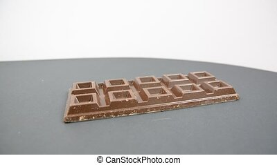 Chocolate bar rotating on neutral background