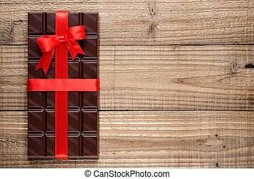 Chocolate bar with ribbon on wooden background