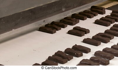 Sweets on a chocolate factory conveyor. - Chocolate bars...