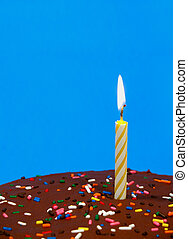chocolate birthday cake with sprinkles and a candle