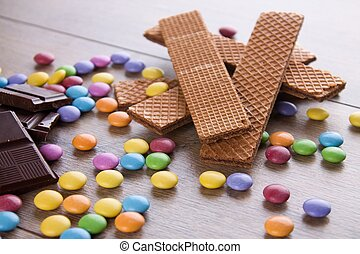 Chocolate biscuits among several color sweets