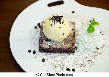 Chocolate brownie with vanilla ice-cream on the dish