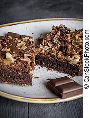 Chocolate brownie with walnuts on a plate.