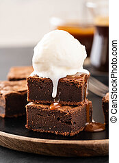 Chocolate brownies with salted caramel, vanilla ice cream. Copy space.
