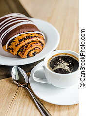 Chocolate bun with cup of coffee