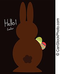 Chocolate bunny holding easter eggs on dark background