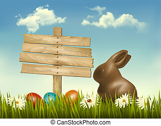 Chocolate bunny with easter eggs and a sign in a field....