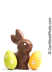 Chocolate bunny with two easter eggs on white background