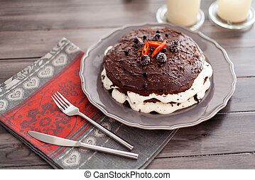 Homemade chocolate cake with white cream, decorated with a blackberry and pepper