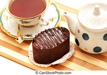 Chocolate cake, kettle and a cup of tea
