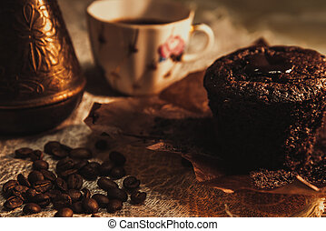 Chocolate cake on parchment with a cup of coffee, copper pots and coffee beans