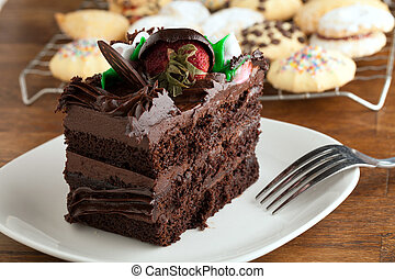 Italian cookies and a decadent slice of chocolate cake with iced flowers and chocolate covered strawberries on a plate with a fork.